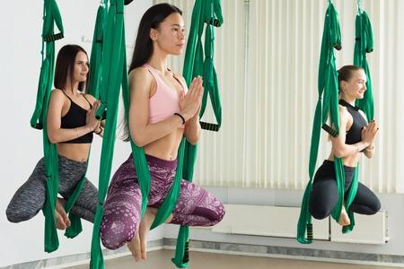 Young women performing antigravity yoga exercise Reklamní fotografie - 101555169
