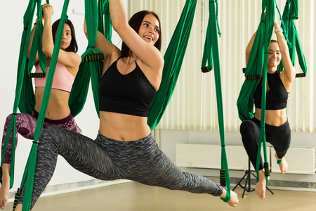 Young women performing antigravity yoga exercise
