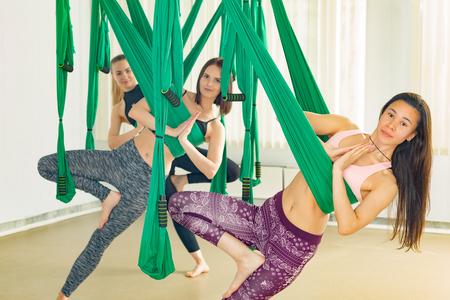 Young women performing antigravity yoga exercise Reklamní fotografie - 101547656