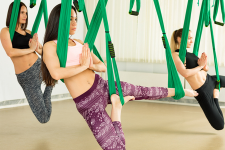 Young women performing antigravity yoga exercise Reklamní fotografie - 101555171