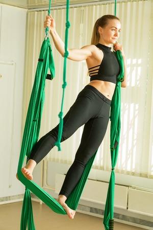 Young woman performing antigravity yoga exercise Reklamní fotografie - 101740859