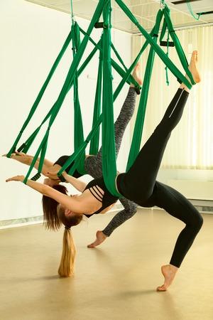 Young women performing antigravity yoga exercise Reklamní fotografie - 101830666