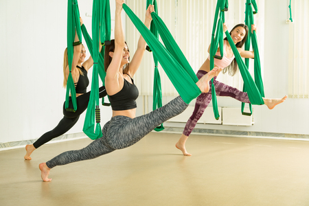 Young women performing antigravity yoga exercise Reklamní fotografie - 101884581