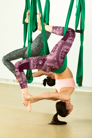 Young woman performing aerial yoga exercise Reklamní fotografie