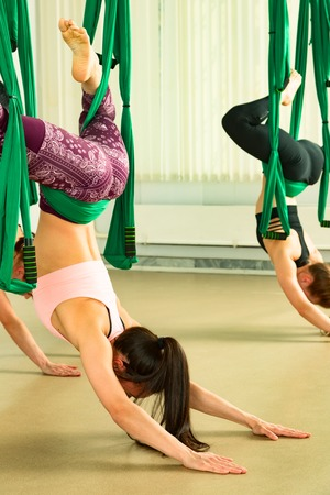 Young woman performing aerial yoga exercise Reklamní fotografie - 101898719