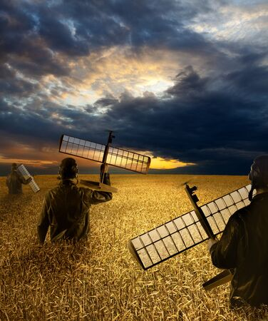 Men on a wheat field hold drones in their hands