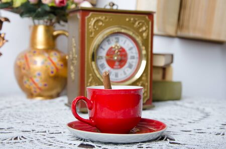 Red cup with cinnamon on a background of watches