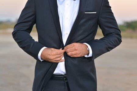 Correct button on jacket, hands close-up, dressing, man's style, stylish man.Elegant young handsome man. Men's jacket, hands cover the button. Business style.