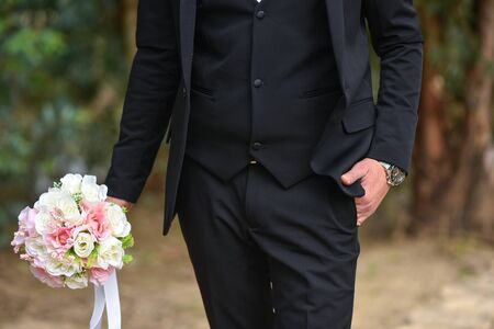 Groom and bouquet in hand close-up, dressing, man's style, stylish man. Elegant young handsome man. Men's jacket, hand cover the button. Business style. Stockfoto