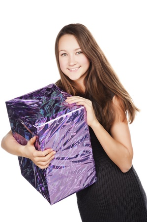 young beautiful young girl smiles, holds a Christmas gift box, festive mood, isolated over white photo