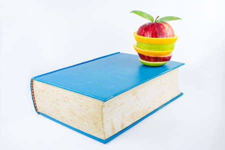 Book and an fruits on a white background  photo