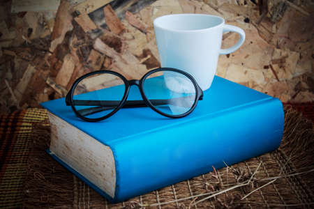 Book and eyeglass on table Stock Photo