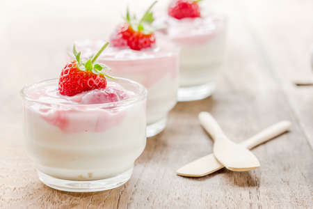 dessert table: strawberry smoothie with strawberries, Delicious refreshing bowl of ripe red fresh strawberries and cream or creamy yoghurt garnished for a tasty dessert