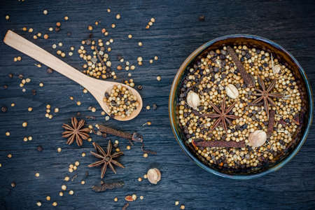 Spices in a ceramic dish on wooden background photo