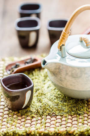 Frame with Asian teapot. cup of tea and teapot on wooden photo