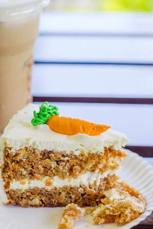 Sweet slice of carrot cake and ice coffee on table photo