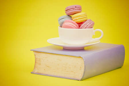 Sweet and colourful french macaroons in cup on book  retro-vintage background photo