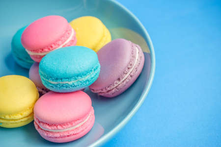 colorful macaroons in plate on blue background photo