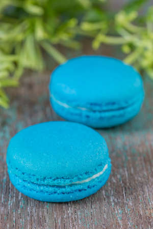buttercream: Light blue French macarons with buttercream on a wooden table