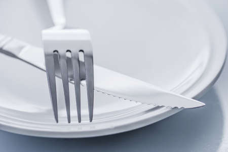 plate with crossed silver knife and fork cutlery, shallow deep of field with focus on tip of fork photo