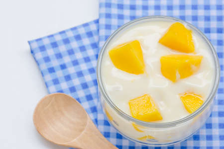 Yogurt with mango  in a glass jars on white background