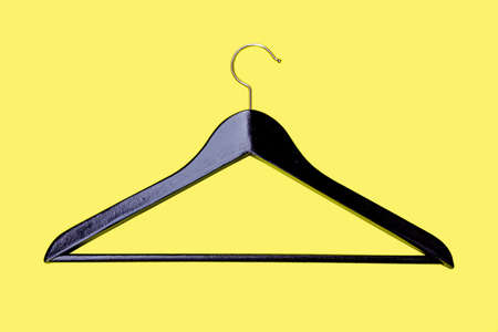 varnished: Hanger - a coat hanger for clothes, from an ebony isolated on a yellow background