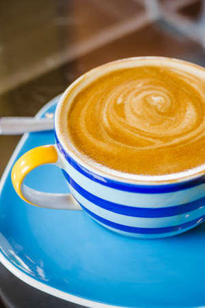 Blue and white cup of latte coffee photo