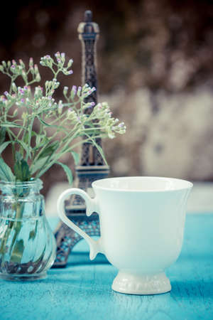 Image of morning tea cup decorated with small eiffel tower and fresh grass flower. vintage style photo