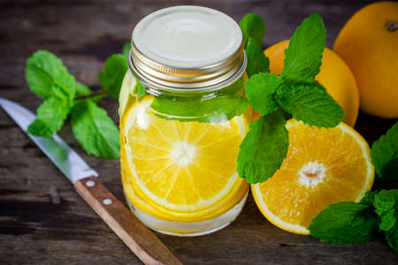 Mug delicious refreshing drink of orange fruit with mint on wooden, infused water photo