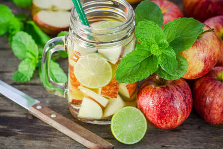 Mug delicious refreshing drink of apple fruits with mint on wooden, infused water photo