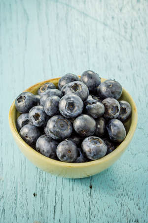 Blueberries in a bowl on a blue wooden table.