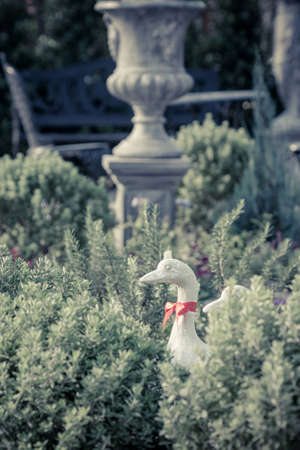 Duck statues in english garden. vintage style photo