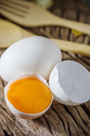 Still life broken white eggs and egg yolk on a wooden rustic background photo