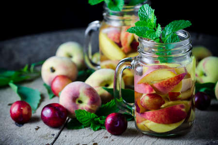Jar delicious refreshing drink of peach fruits and plum  with mint on wooden, infused water photo