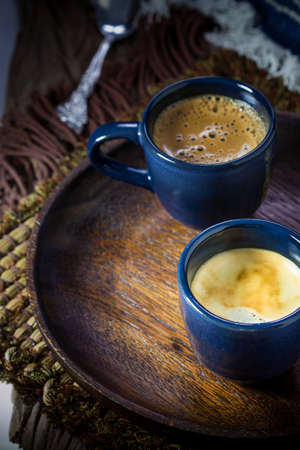 Two blue cups of espresso on wooden plate