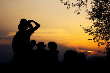 Silhouette of travelers with camera during sunset at That Phu Si and Wat tham Phu Si, Luang Prabang Laos. photo
