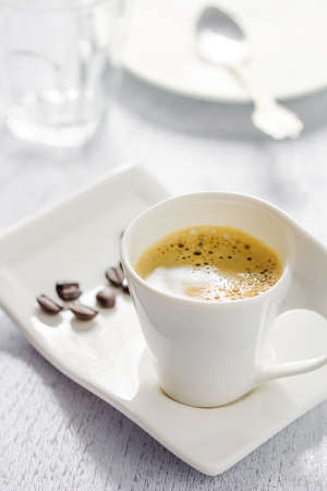 White cup of espresso on white wooden background photo