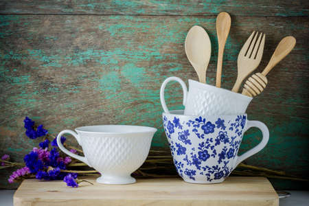 Wooden kitchen utensils and coffee cups on wooden background photo