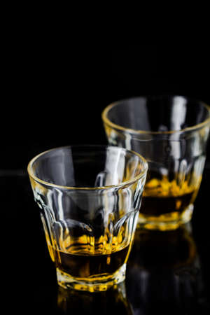 Two glasses of whiskey on black blackboard photo