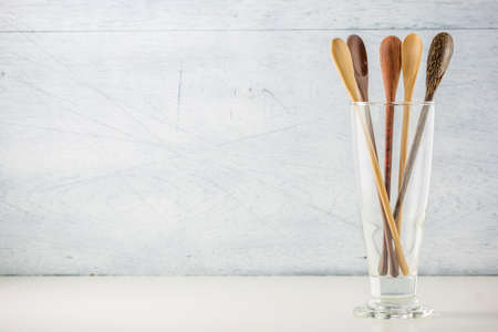 daily use item: kitchen utensils, wooden spoons on white wooden background