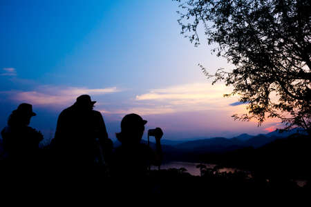 si: Silhouette of travelers with camera during sunset at That Phu Si and Wat tham Phu Si, Luang Prabang Laos.