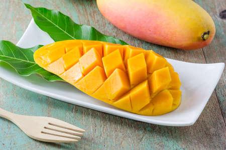 mango: fresh mango fruit in white plate on wooden table Stock Photo