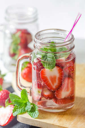 refreshing: Mug delicious refreshing drink of strawberry on wooden, infused water
