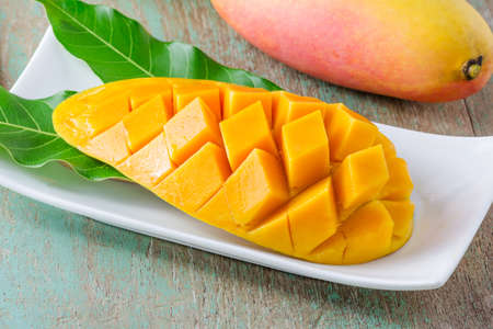 tropical food: fresh mango fruit in white plate on wooden table Stock Photo