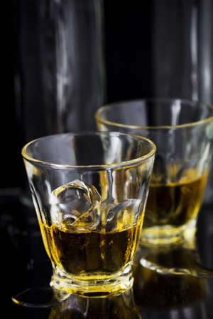 table glass: Two glasses of whiskey with ice cubes on black background Stock Photo