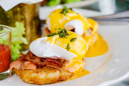 english breakfast: Eggs Benedict- toasted English muffins, ham, poached eggs, and delicious buttery hollandaise sauce