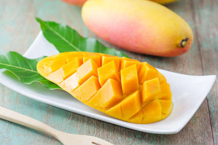 fresh mango fruit in white plate on wooden table Stock Photo