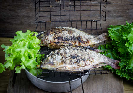nile tilapia: Salt crusted grilled nile tilapia fish on grate Stock Photo