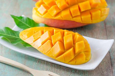 plato de comida: fresca fruta del mango en plato blanco sobre la mesa de madera