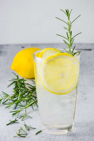 Lemonade with fresh lemon and rosemary in glass on wooden background